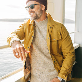 fit model wearing The Lombardi Jacket in Mustard Dry Wax, smiling on ferry