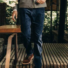 our fit model wearing The Camp Pant in Indigo Corduroy—standing on wooden deck