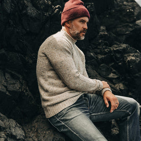 our fit model wearing The Seafarer Sweater in Natural Donegal—sitting on a rock