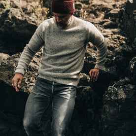 our fit model wearing The Seafarer Sweater in Natural Donegal—looking down near rocks
