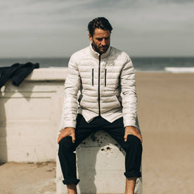 our fit model wearing The Taylor Stitch x Mission Workshop Farallon Jacket in fog—sitting near beach