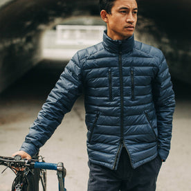out fit model wearing The Taylor Stitch x Mission Workshop Farallon Jacket in Midnight Blue—standing with bike