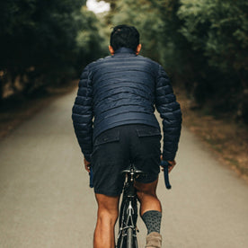 out fit model wearing The Taylor Stitch x Mission Workshop Farallon Jacket in Midnight Blue—back shot riding bike