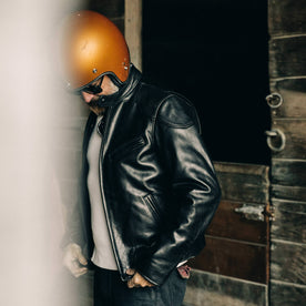 our fit model wearing The Band Collar Moto Jacket—looking down, helmet on