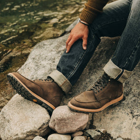 our fit model wearing The Scout Boot in Espresso Grizzly—sitting on rocks