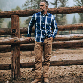 fit model wearing The Democratic All Day Pant in Rustic Oak Organic Selvage, near fence