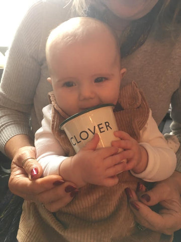 Clover holding an enamel cup with her name engraved