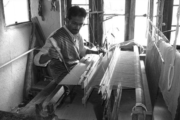 An image showing an artisan working on a traditional loom in the production of the cashmere pashmina.