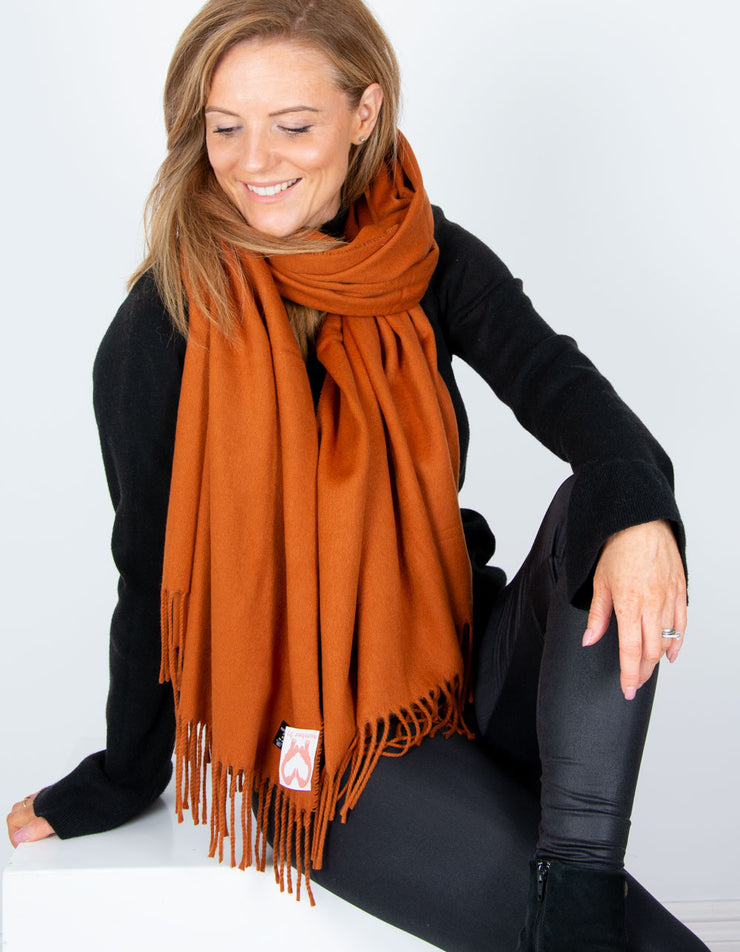an image showing an orange blanket scarf