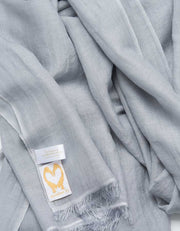 A close up image of a wool silk mix pashmina in silver grey