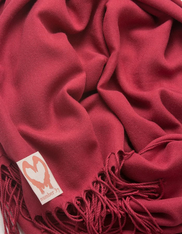 an image showing a close up of a pashmina in Mulberry red
