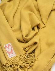 an image showing a close up of a pashmina in Mustard