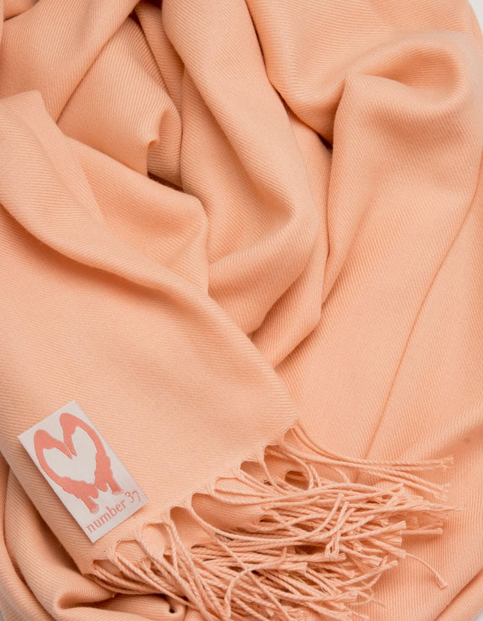 an image showing a close up of a pashmina in Peach Pink