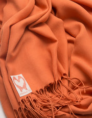 an image showing a close up of a pashmina in Pumpkin orange