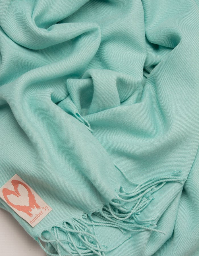 an image showing a close up of a pashmina in Turquoise