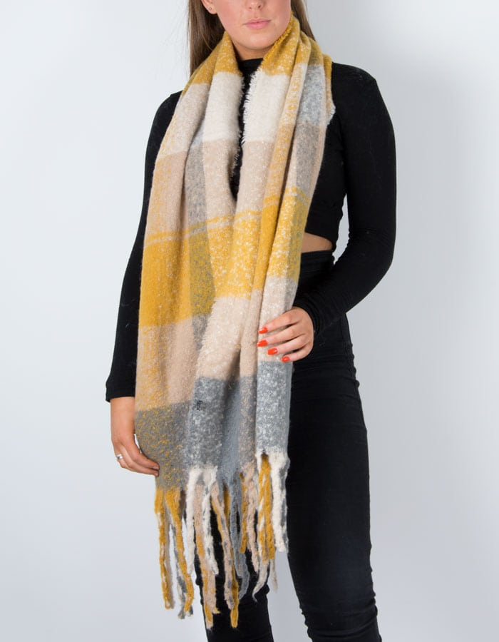 an image showing a winter knit check scarf with mustard tassel