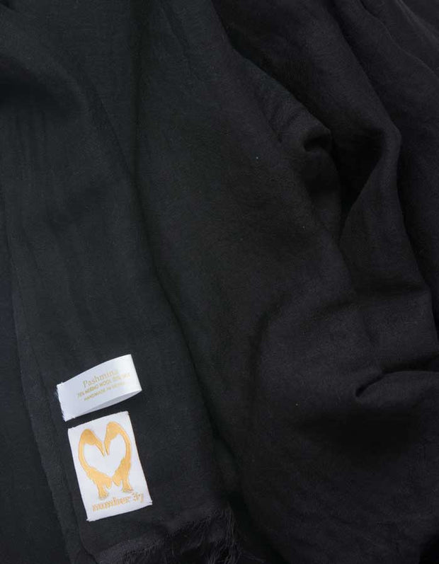 A close up image of a wool silk mix pashmina in Black