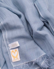 A close up image of a wool silk mix pashmina in blue