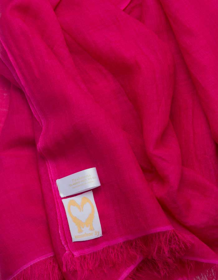 A close up image of a wool silk mix pashmina in hot pink