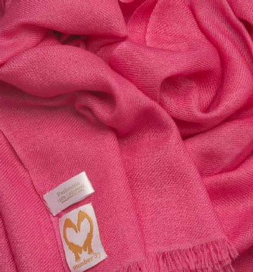 An image showing a cashmere wedding pashmina in hot pink close up