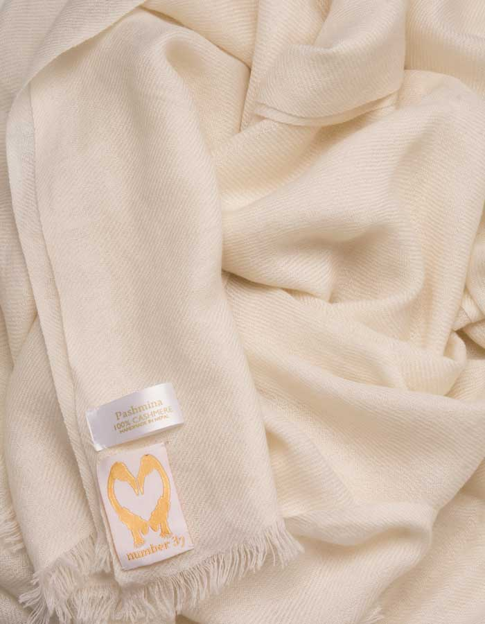 an image showing a pure cashmere pashmina scarf in ivory