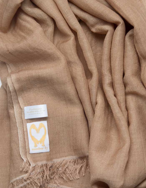 A close up image of a wool silk mix pashmina in light brown