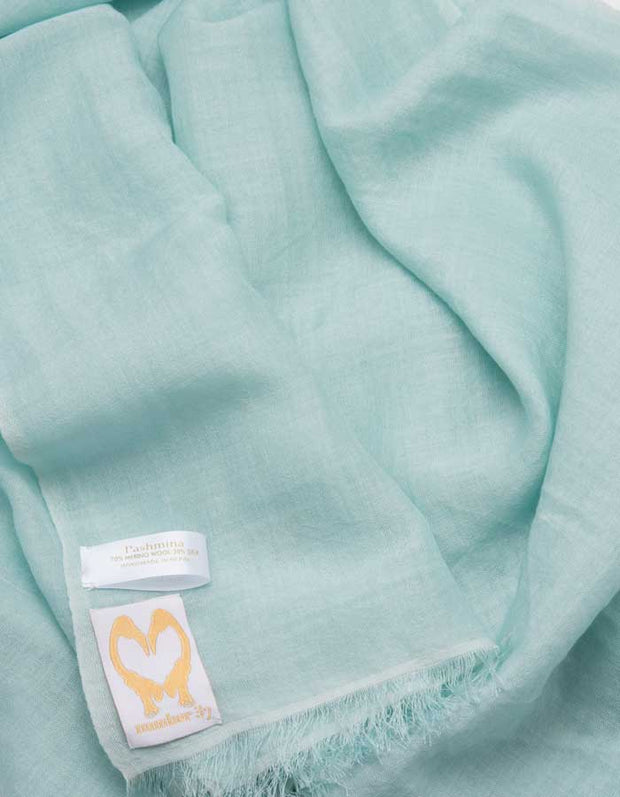 A close up image of a wool silk mix pashmina in mint green