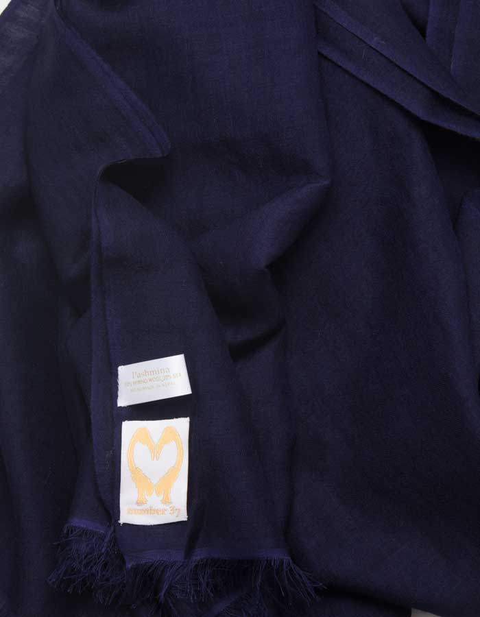 A close up image of a wool silk mix pashmina in navy blue