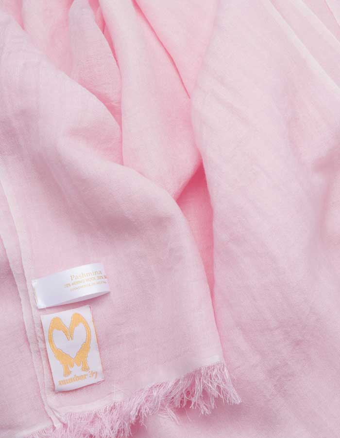 A close up image of a wool silk mix pashmina in pale pink