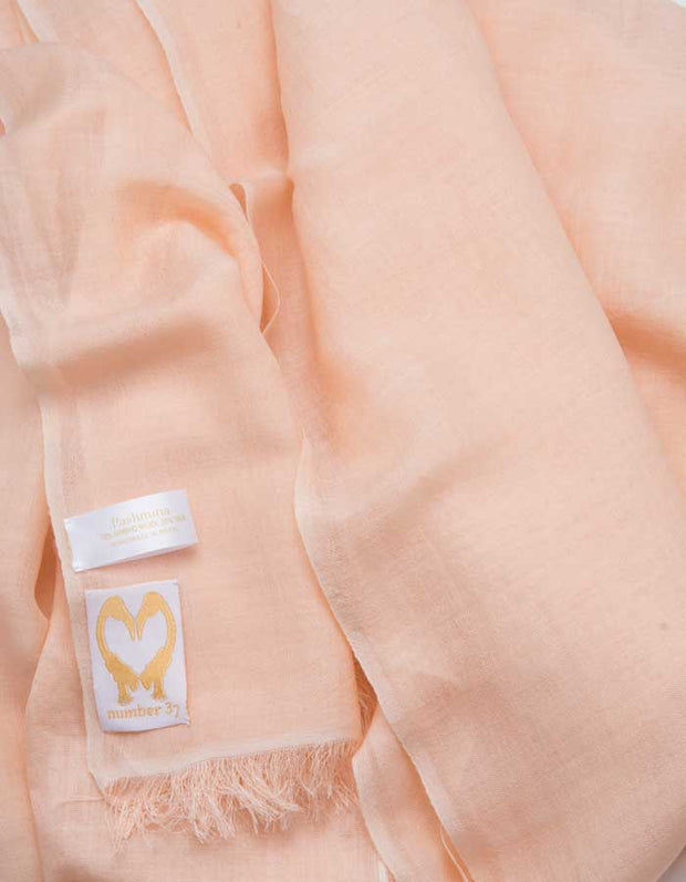 A close up image of a wool silk mix pashmina in peach
