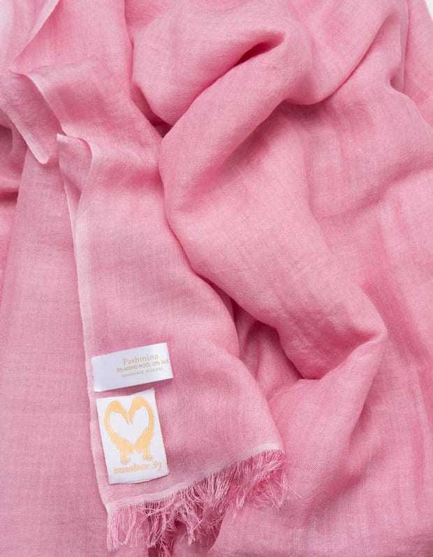 A close up image of a wool silk mix pashmina in pink