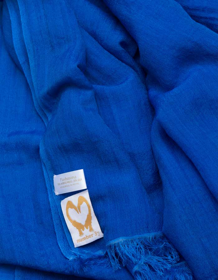 A close up image of a wool silk mix pashmina in Royal blue