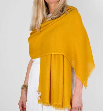 an image showing a cashmere wedding pashmina in mustard