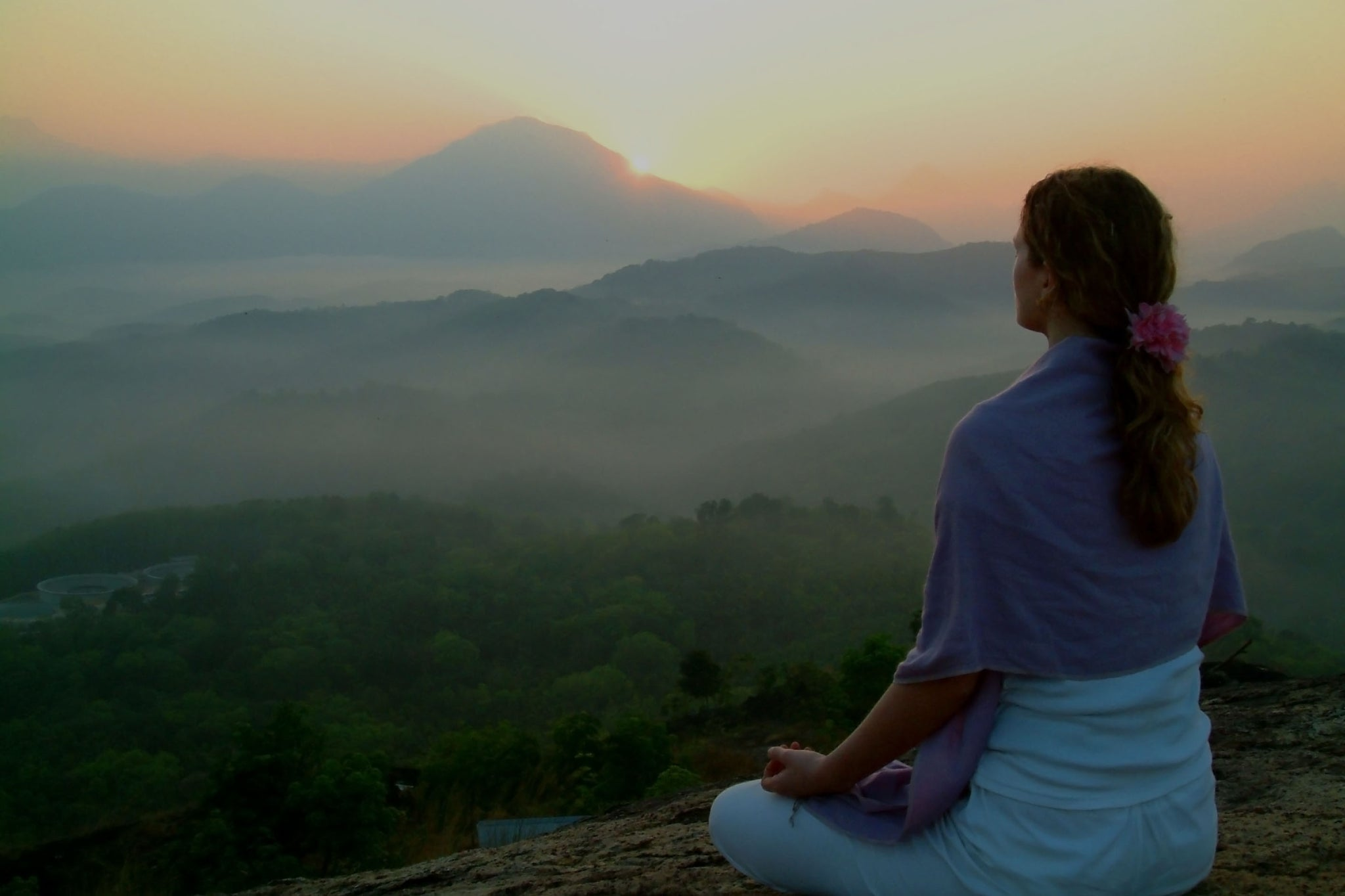 woman meditates in mountains