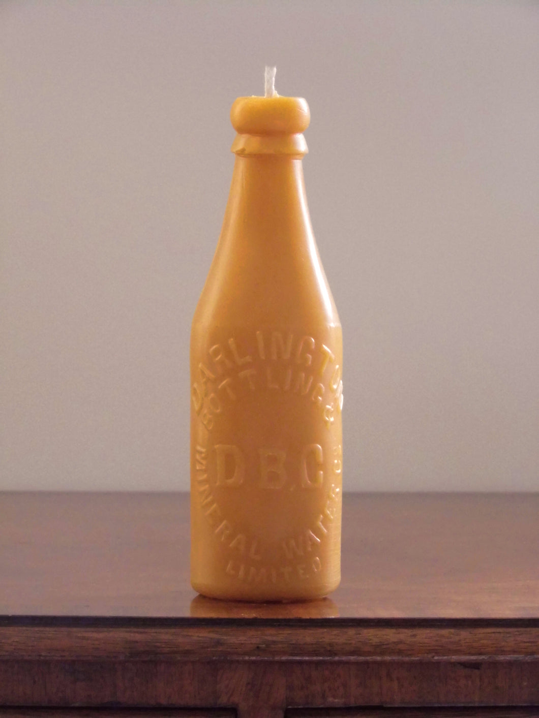 beeswax candle in the shape of an antique Darlington bottle