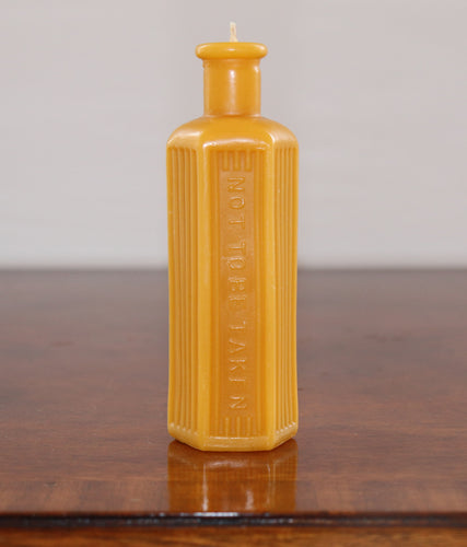 beeswax candle in the shape of an old poison bottle