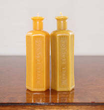 Load image into Gallery viewer, two beeswax candles in the shape of an old poison bottle
