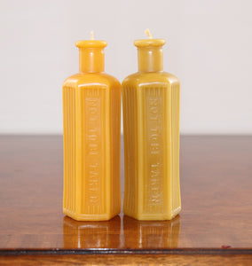 two beeswax candles in the shape of an old poison bottle