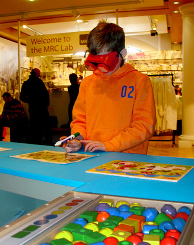 Young boy trying a game task with low vision to simulate impairment