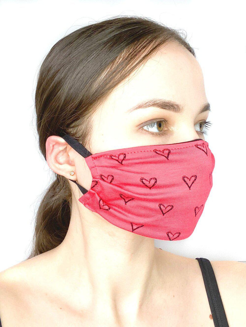 Side view of a girl wearing a custom size organic cotton face mask in coral hearts print