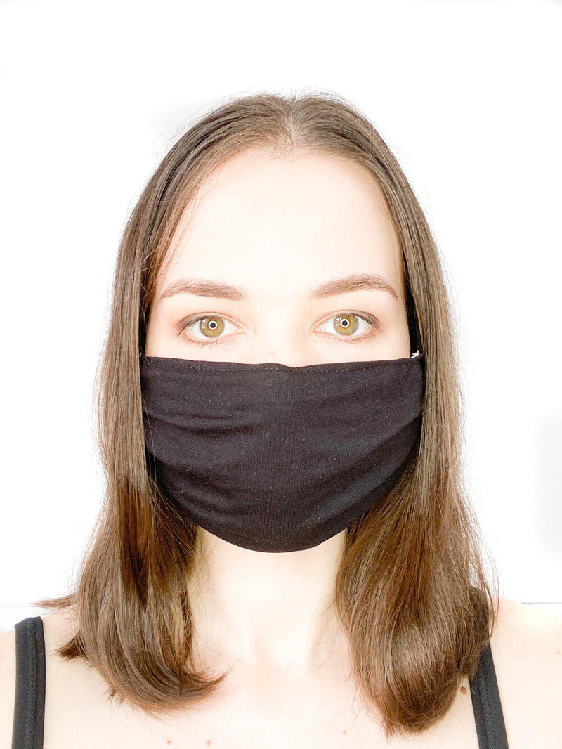 A girl wearing a custom size organic cotton face mask in black colour