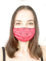 A girl wearing a custom size organic cotton face mask in coral hearts print