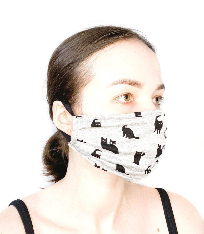 Side view of a girl wearing a custom size organic cotton face mask in cat print