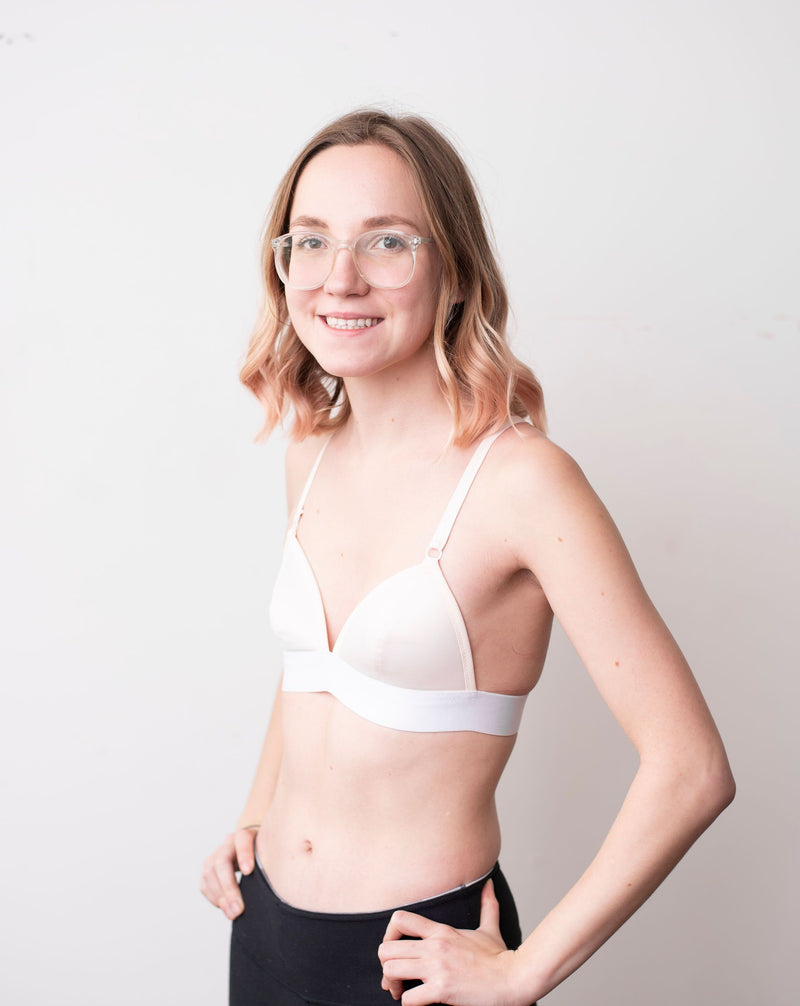 Haley from Rubies Bras, a female with medium blond hair wearing a peach and white wirefree bra from our petites collection. Side body shot on white back drop.