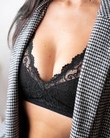 Ruhee with Rubies Bras, a female with long black hair wearing a black and white checkered blazer and a black scalloped lace wirefree bra with deep plunge v neckline. Half body close up shot on white back drop.
