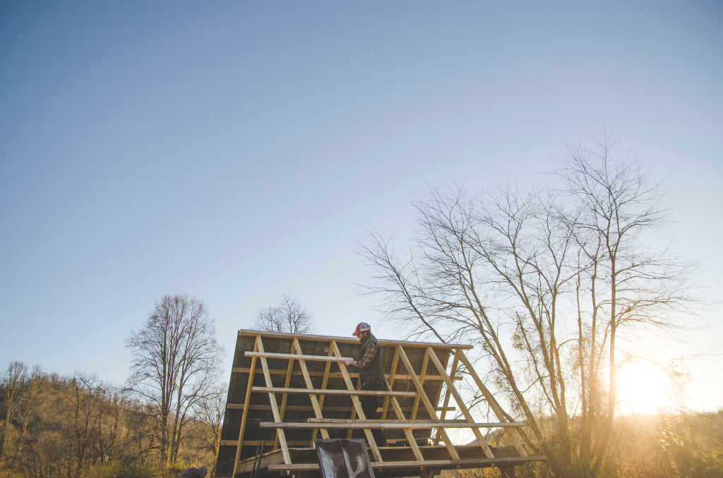 "Brandon Hughes building a ""squirrel's nest"" off grid shelter along the French Broad River."