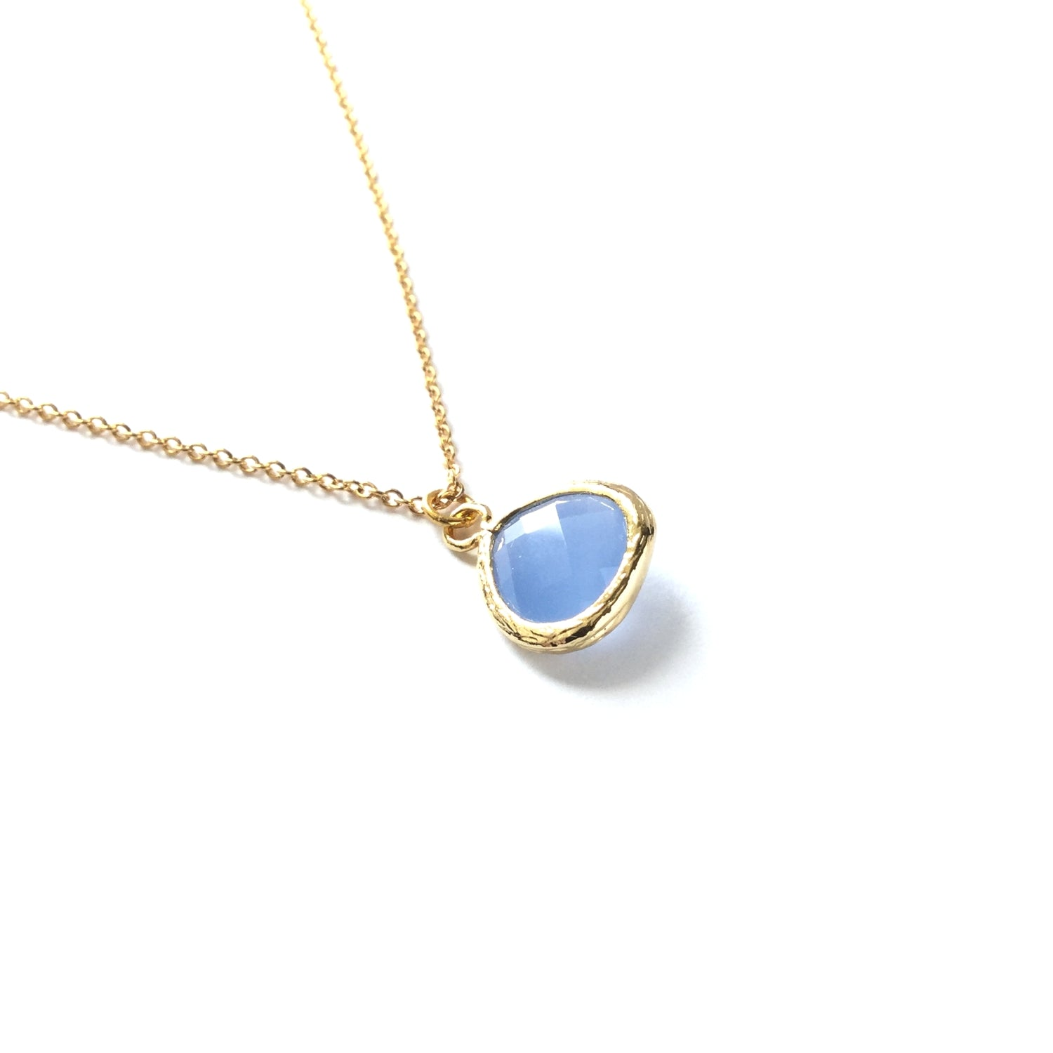 Gold plated framed ice blue faceted glass teardrop pendant on a gold plated chain necklace