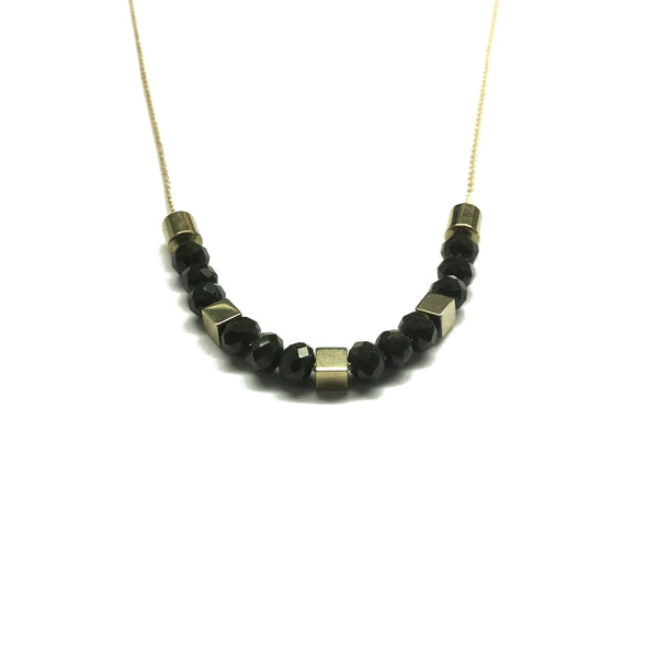 Gold brass tube bead with black faceted glass beads and gold square hematite bead spacers on a thread necklace