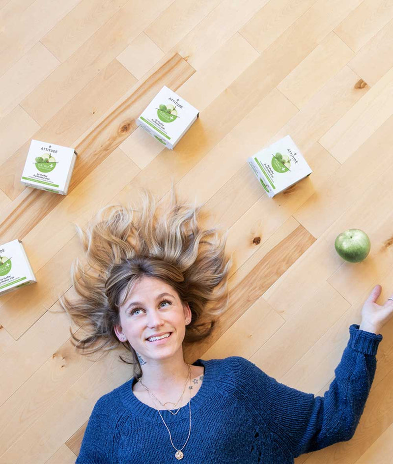 Smiling woman lying on the floor with an apple and 4 ATTITUDE Air Purifiers surrounding her head_en?_team?