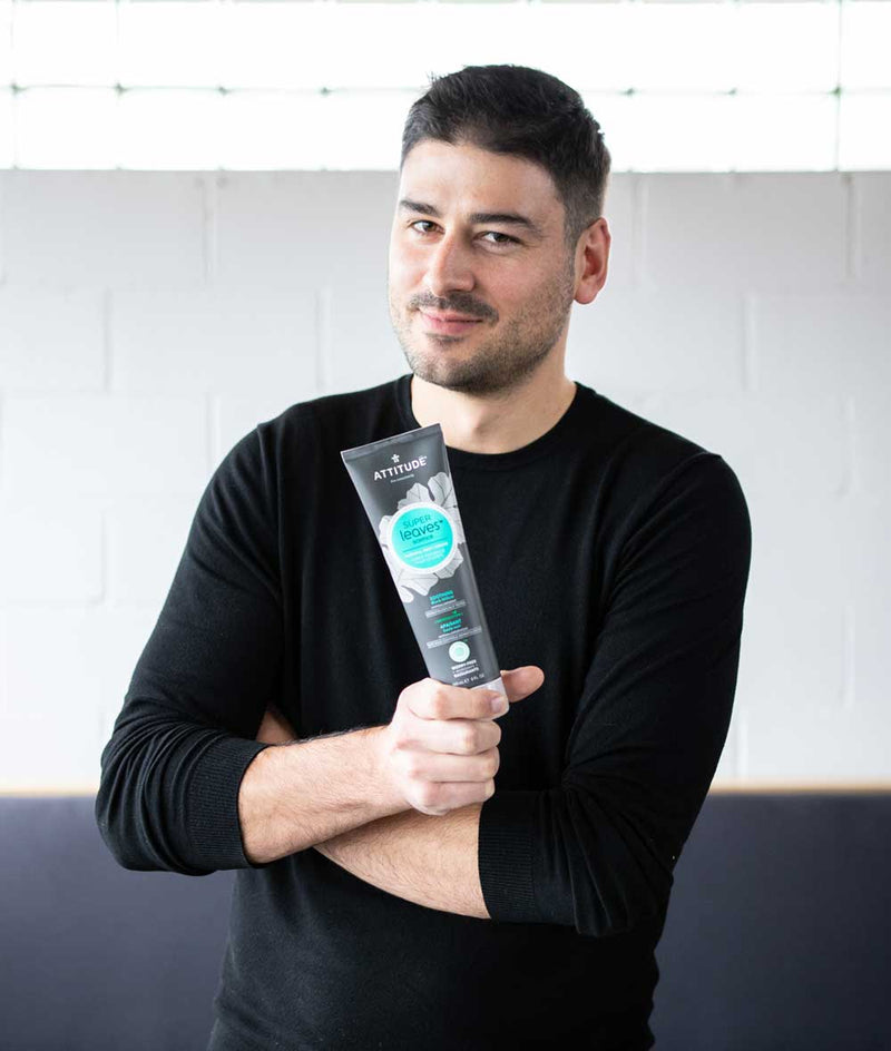 Man smiling while holding ATTITUDE Super Leaves Soothing Body Cream For Men_en?_team?